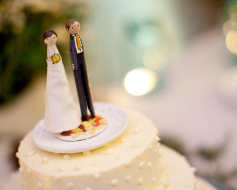 Cream wedding cake with couple on top