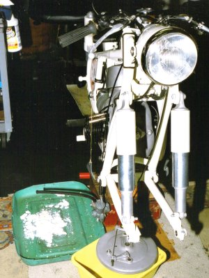 frontal of vintage 1955 BMW R50; to right of motorcycle is a pan heaped with salt.