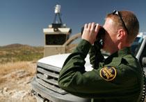 Photo of Border Patrol Agent looking through Binoculars