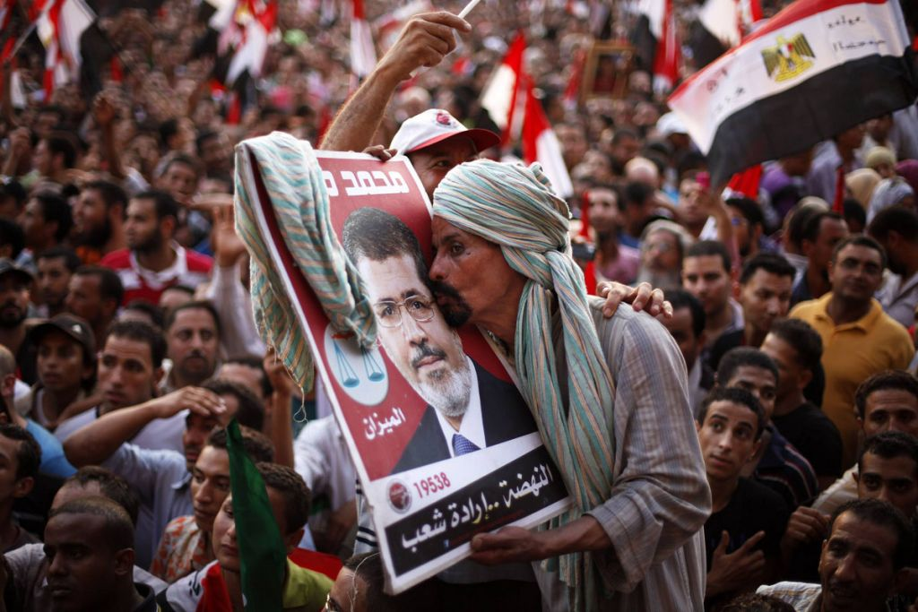 A supporter of Muslim Brotherhood's presidential candidate Mohamed Morsy kisses his picture during a celebration of his victory at the election at Tahrir Square in Cairo June 24, 2012.  REUTERS/Suhaib Salem (EGYPT - Tags: POLITICS CIVIL UNREST) ORG XMIT: SJS11