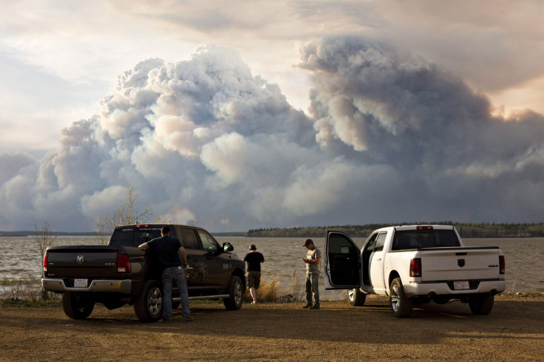 Evacuees watch the wildfire near Fort McMurray on Wednesday. The wildfire has already torched 1,600 homes and buildings.