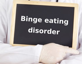 binge eating disorder written on a small blackboard chalkboard, being held by a doctor wearing a white coat and latex gloves