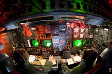 Lower deck of a B-52, with instruments and displays featuring dominantly on the aircraft's side wall. This station is manned by two crew members.