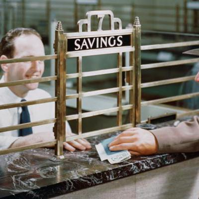 Bank teller and savings account customer - Petrified Collection / Getty Images