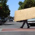 Workers carry plywood across International Blvd. in preparation for possible protests after the Mehserle verdict. (CALIFORNIA BEAT PHOTO)