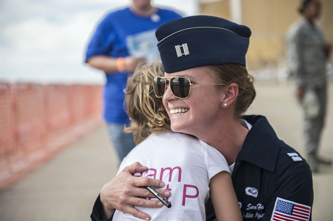 Air Force Capt. Sara Harper hugs a special guest at Davis-Monthan Air Force Base in Tucson, Ariz., March 11, 2016. Harper is a pilot assigned to the Thunderbirds, the Air Force's air demonstration squadron. Air Force photo by Senior Airman Jason Couillard