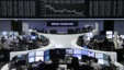 FILE - Traders work at their desks in front of the German share price index, DAX board, at the stock exchange in Frankfurt, Germany, Feb. 16, 2016.