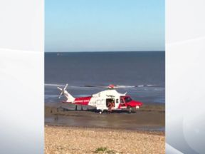 A helicopter taking part in the search for a pilot after a light plane crash lands on Winchelsea beach