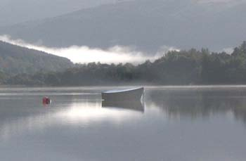 A rowing boat on a loch with mountains and forest background