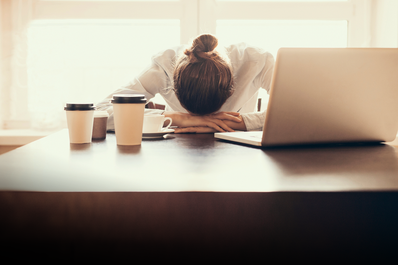 Woman overwhelmed by emails and meetings with her head down on the desk