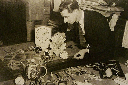 Melbourne Investigations Officer Ray Funge with a selection of seized timepieces in the mid-1950s.