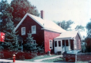 311 Nahatan St in the late 1970's. The front of the house has been painted red but the right side still has some brown shingles.