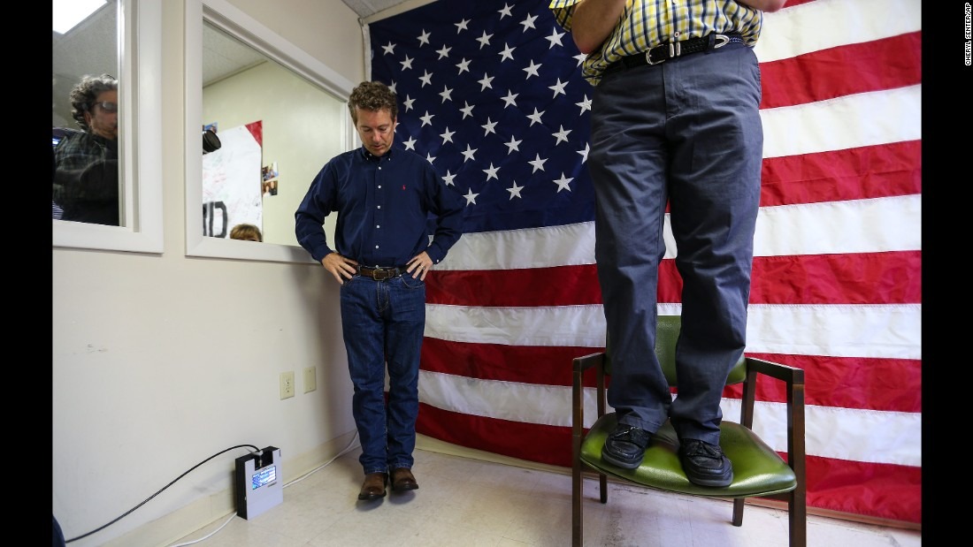 """U.S. Sen. Rand Paul, <a href=""""http://www.cnn.com/2015/04/07/politics/rand-paul-president-2016/"""" target=""""_blank"""">a Republican presidential candidate</a> from Kentucky, looks down as New Hampshire Sen. Andy Sanborn, standing on a chair, makes opening remarks at the opening of Paul's campaign office in Manchester, New Hampshire, on June 5, 2015. Paul, the son of former U.S. Rep. Ron Paul, has carefully built a brand of mainstream libertarianism since riding the tea party wave into the Senate in 2010."""