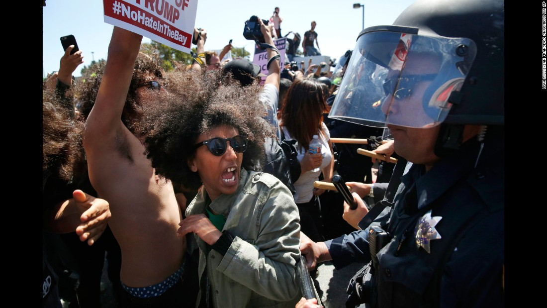 """Protester Biseat Yawkal yells as she is pushed by police outside of the California Republican Convention on April 29, 2016. Trump protesters -- some of whom wore bandanas over their faces and carried Mexican flags -- <a href=""""http://www.cnn.com/2016/04/29/politics/donald-trump-protests-republican-convention-california/"""" target=""""_blank"""">blocked off the road </a>in front of the Hyatt Regency, forcing Trump's motorcade to pull over along a concrete median outside the hotel's back entrance. Trump and his entourage got out and walked into the building."""