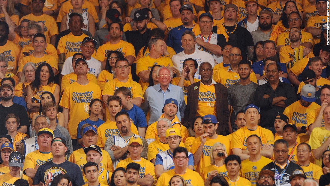 Sanders, at center in the light-blue shirt, watches a playoff basketball game in Oakland, California, on May 30, 2016. The candidate, campaigning for the state's primary, saw the Golden State Warriors win Game 7 of the NBA's Western Conference Finals.