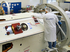 A technician inspects one of the two satellites