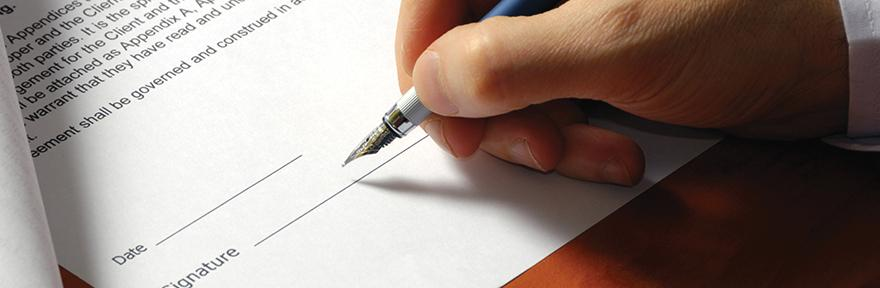 Image of a hand signing on paper with a pen