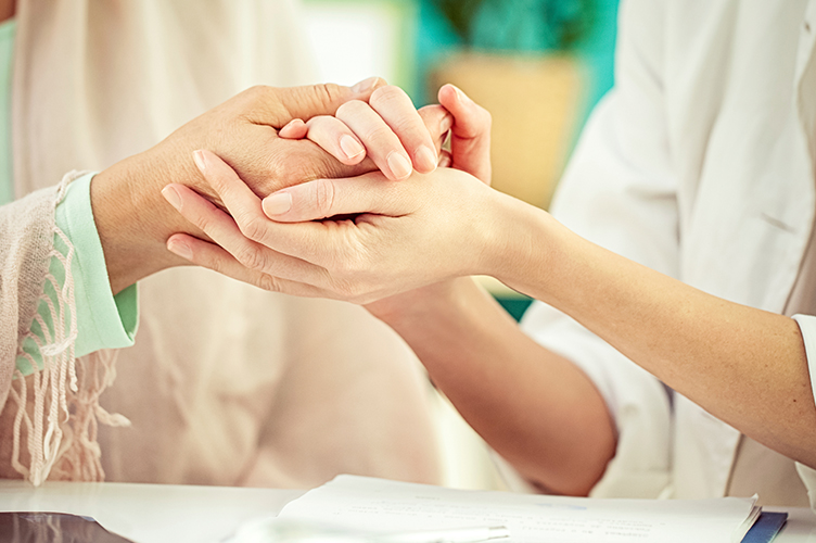 a close up image of two people holding each others hands in a comforting way