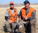 Photo of two hunters wearing hunter orange with recently harvested deer. Rifle with scope in the foreground.