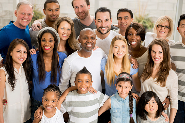 an image of a diverse group of people ranging in age from 7 years old to 70 years old standing together and smiling