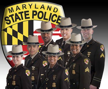 A diverse group of Maryland State Troopers in front of an image of the Maryland State Police logo