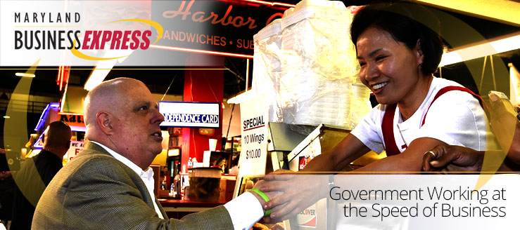Maryland Business Express - Government Working at the Speed of Business. Photo of Governor Larry Hogan meeting with an employee at the Lexintgon Market in Baltimore
