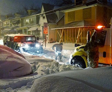 Soldiers from the 110th Information Operations Battalion, while supporting the Annapolis area, work to free an ambulance from being stuck in the snow on Jan. 24, 2016.