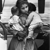Young Cuban refugee holding her dolls in a Florida airport, circa 1961.