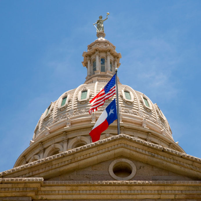 State of Texas Capitol dome with U.S. and Texas flags