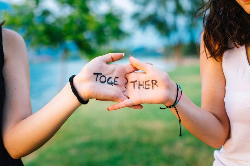 Teen girls hands say together
