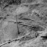 Army bulldozers constructing the Ledo Road cut a path through a hillside in the Indian jungle