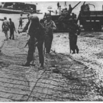 Engineers lay out roads on soft sand for heavy vehicles and equipment to come ashore on 6 June 1944.