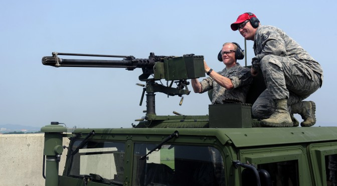 Chief Master Sgt. of the Air Force James A. Cody fires an M250 caliber machine gun as he is supervised by Staff Sgt. Brandon Johnson, 8th Security Forces Squadron combat arms instructor, as part of a two-day tour at Kunsan Air Base, Republic of Korea, July 2, 2015. Cody engaged with Wolf Pack Airmen to answer questions and give insight on key Air Force topics and changes. (U.S. Air Force photo by Staff Sgt. Nick Wilson/Released)
