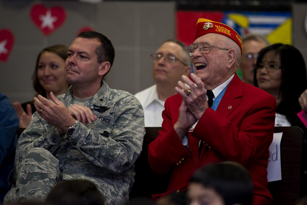 """U.S. Air Force Brig. Gen. Scott Kindsvater, 82nd Training Wing commander, sits beside Hershal """"Woody"""" Williams, Iwo Jima survivor and Medal of Honor recipient, during the Iwo Jima Survivors 70th Reunion at Sheppard Air Force Base, Texas, Feb. 13, 2015. Kindsvater and Williams applaud for the Sheppard Elementary School students after they delivered their speeches. This will be the last reunion of the Iwo Jima survivors. (U.S. Air Force photo by Senior Airman Kyle Gese/Released)"""