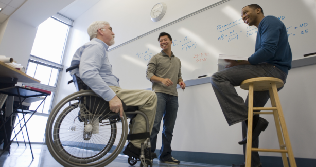 3 people in a classroom one in a wheelchair at a whiteboard