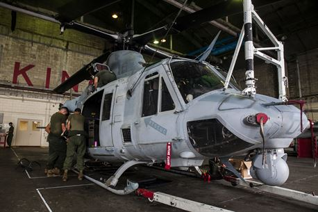 """Marines begin the installation of newly received auxiliary fuel tanks for the UH-1Y Venom at Marine Corps Air Station Futenma, Okinawa, Japan, June 14, 2016. """"We have never installed these in the fleet, which the Marines here with the engineers are accomplishing today,"""" said Maj. Carl A. Bailey, the executive officer of Marine Light Attack Helicopter Squadron 469, Marine Aircraft Group 39, 3rd Marine Aircraft Wing, currently assigned to Marine Aircraft Group 36, 1st Marine Aircraft Wing through the Unit Deployment Program. """"These are going to extend our range, our time on station and enable us to self-deploy throughout the Pacific area of operations. Our goal is to self-deploy to the Philippines, and if we can do that, we will not need C-17s, C-5s or any other aircraft. We won't have to break down our own aircraft, we will just strap on the tanks and go."""" The Marines are with HMLA 469. (U.S. Marine Corps photo by Cpl. Tyler S. Giguere)"""
