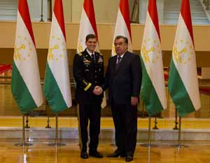 Two men standing in front of flags. (Photo Credit: State Department)
