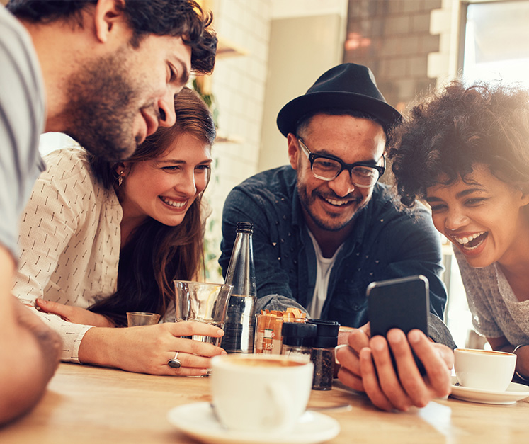 A group of young adults gathered around a kitchen table looking at a mobile phone.