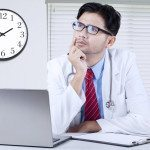 Image of male doctor sitting in the clinic while thinking something and looking upward with laptop on the table