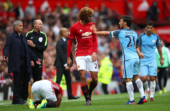 MANCHESTER, ENGLAND - SEPTEMBER 10: David Silva of Manchester City (R) pushes Marouane Fellaini of Manchester United (L) after a challenge during the Premier League match between Manchester United and Manchester City at Old Trafford on September 10, 2016 in Manchester, England. (Photo by Clive Brunskill/Getty Images)