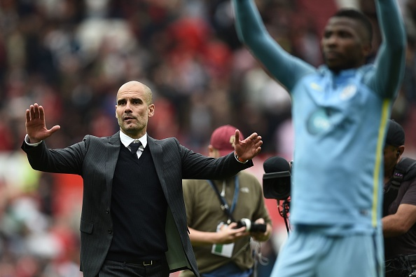 Manchester City's Spanish manager Pep Guardiola and his players celebrate on the pitch after the English Premier League football match between Manchester United and Manchester City at Old Trafford in Manchester, north west England, on September 10, 2016. Pep Guardiola savoured a derby success over arch-rival Jose Mourinho on Saturday as Manchester City beat Manchester United 2-1 in an engrossing Premier League clash. / AFP / Oli SCARFF / RESTRICTED TO EDITORIAL USE. No use with unauthorized audio, video, data, fixture lists, club/league logos or 'live' services. Online in-match use limited to 75 images, no video emulation. No use in betting, games or single club/league/player publications. / (Photo credit should read OLI SCARFF/AFP/Getty Images)