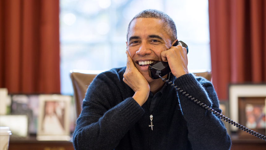 President Obama smiles while speaking on the phone in the Oval Office