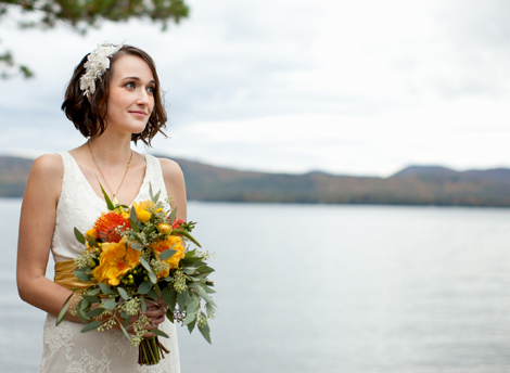 A bride by a lake holding an orange and yellow bouquet
