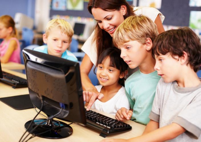 A classroom setting with a taecher, a computer and kids