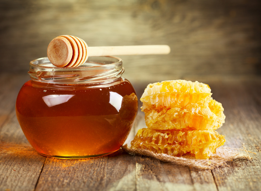 jar of honey with honeycomb on wooden table Stop Snoring