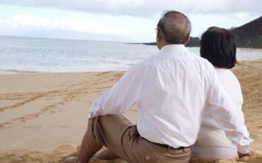 image of an older couple sitting on the sand at the beach