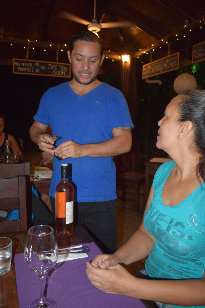 Allan Vargas uncorks a bottle of rosé.