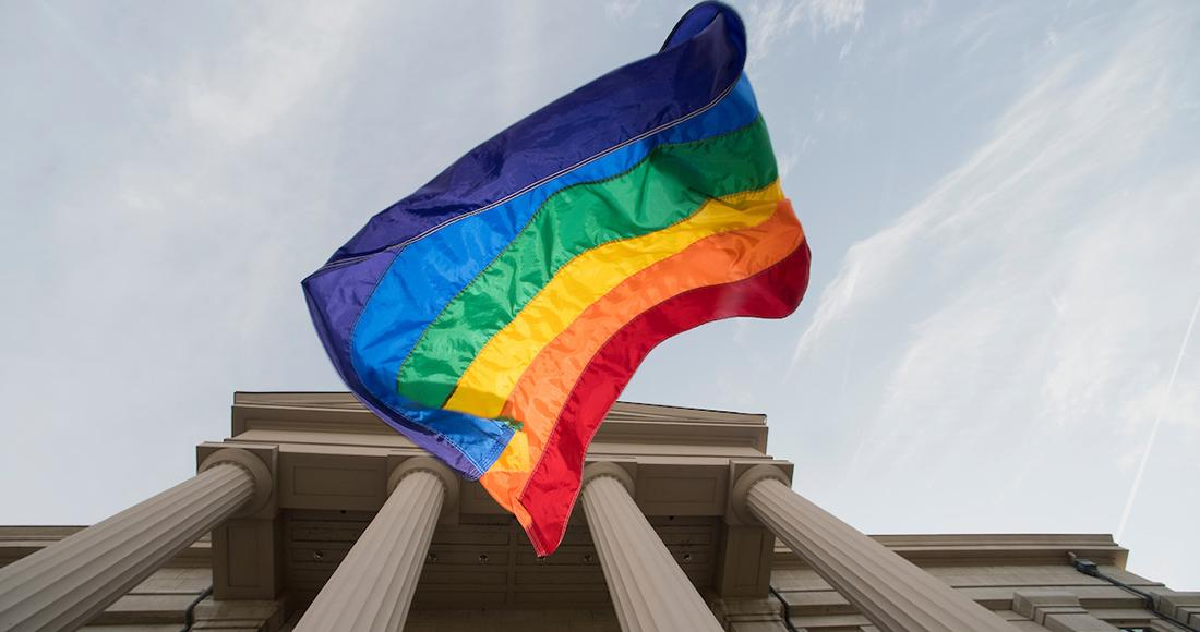 rainbow flag with old cap in background