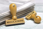 "Stock image of a ""Regulations"" stamp and a stack of papers"