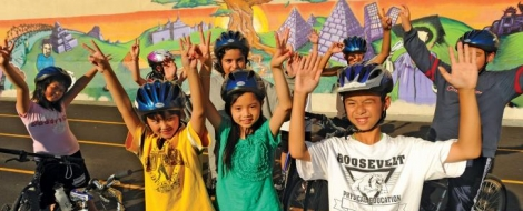 Children wearing bike helmets and with bikes raise their arms above their heads